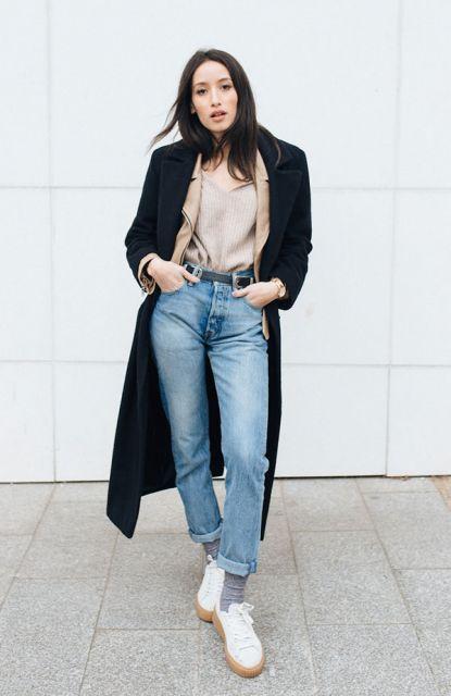 Modelo usa calça jeans, camisa, trench coat preto longo e tenis branco com meia soquete cinza.