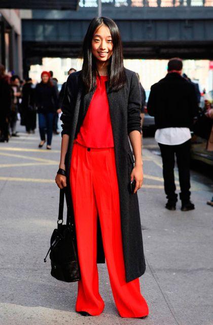 Modelo usa casaco preto longo, macacão vermelho e bolsa preta.
