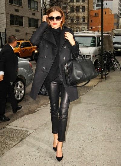 Modelo usa calça de couro preta, blusa preta, casaco trench coat preto, bolsa e scarpin também em preto.