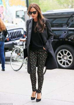 Modelo usa calça estampada, scarpin preto, blusa preta e casaco tench coat preto.