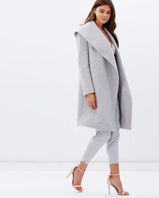 Modelo veste calça cinza, trench coat cinza claro e sandália tiras finas branca.