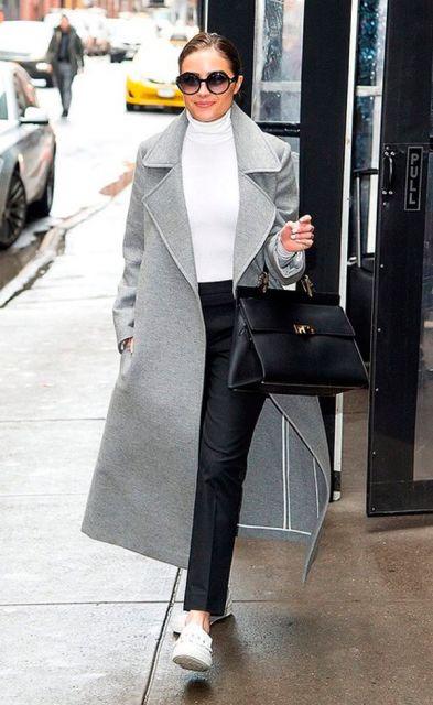 Modelo usa trench coat cinza longo, calça jeans escura, blusa e tênis branco com bolsa preta.