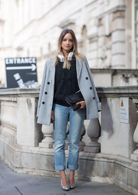 Modelo usa calça jeans, blusa preta, trench coat cinza e sapato cinza claro scarpin.