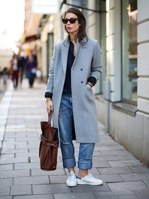 Modelo veste calça jens, tenis branco, blusa azul marinho, casaco trench coat cinza claro e bolsa marrom.