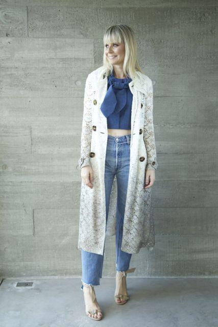 Modelo usa blusa cropped azul escuro, calça jeans, sandalia nude e casaco trench coat cinza claro também.