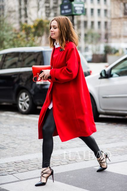 Modelo usa casaco trench coat vermelho, calça preta e sapato estilo scarpin de detalhes preto.