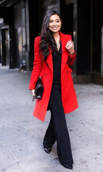 Modelo usa calça preta, blusa preta, bolsa e sapato no mesmo tom e casaco trench coat vermelho.