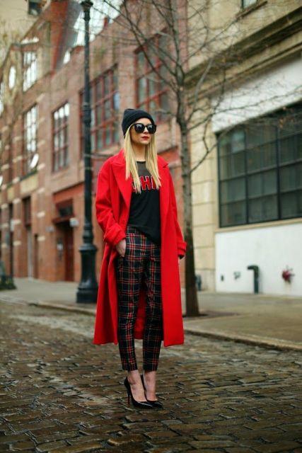 Modelo usa calça xadrez, blusa preta, casaco trench coat vermelho e scarpin preto.
