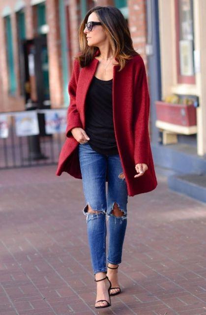 Modelo usa calça jeans, blusinha preta, sandália nudist preta e trench coat vermelho escuro.