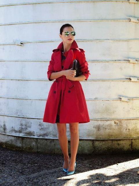 Modelo usa trench coat estilo vestido com scarpin e bolsa de mao carteira preta.