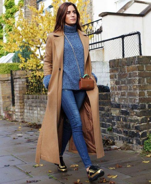 Modelo usa calça jeans azul, blusa azul de gola, tenis preto com dourado e trench coat (casaco) bege escuro.