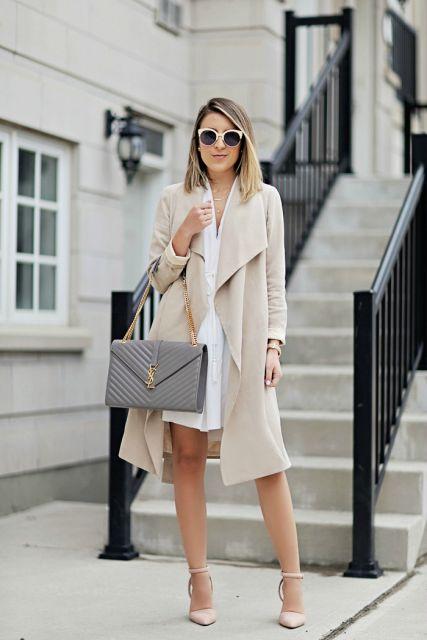 Modelo usa vestido branco, bolsa cinza, sapato bege e trench coat bege clarinho.