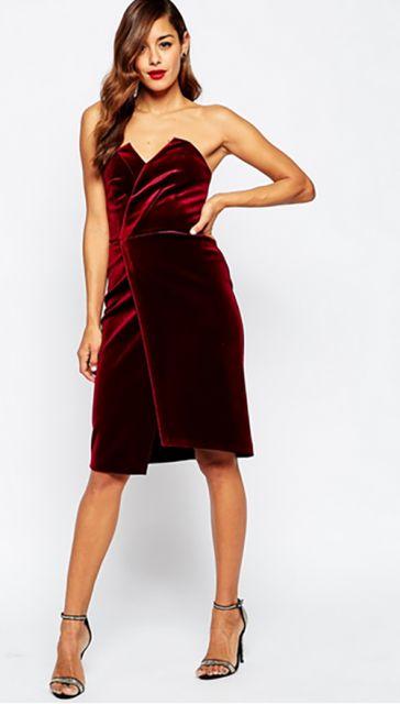 Modelo usa vestido de veludo vermelho vinho, com sandália preta.