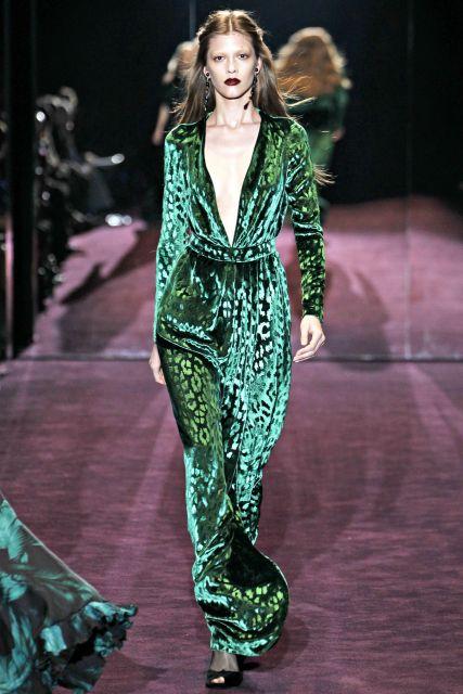 Modelo veste vestido de veludo verde longo com decote e manga longa.