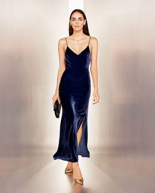 Modelo usa veztido longo azul de veludo, com bolsa preta e sandália.