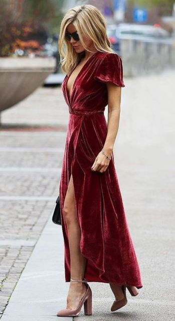 Modelo usa vestido de manguinhas soltinhas, acinturado com decote e fenda na cor vermelha combinado com sandália em cores terrosas.