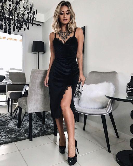 Modelo veste vestido veludo preto de alcinhas, com fenda e rendinha curto, colar prata e sapato preto.