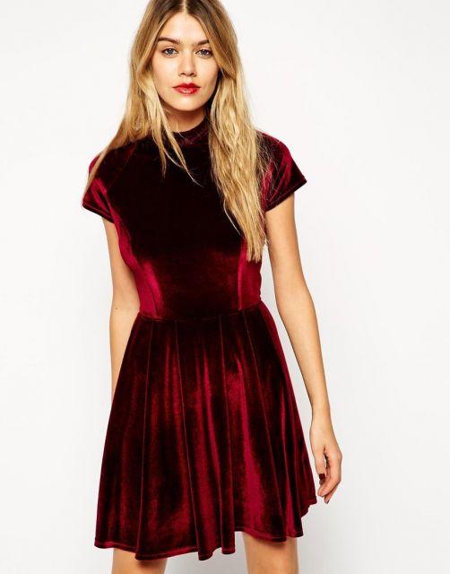 Modelo usa vestido godê vermelho escuro de veludo sem decote.