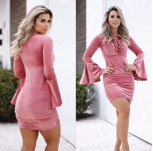 Modelo usa vestido rosa com ilhós no busto, curto , manga flare.