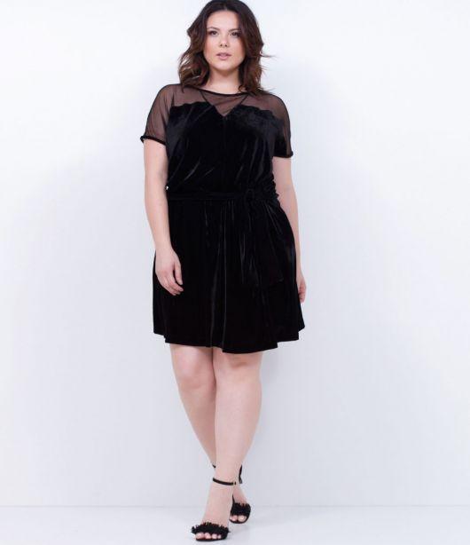 Modelo usa sandália preta e vestido de manguinhas de veludo preto.