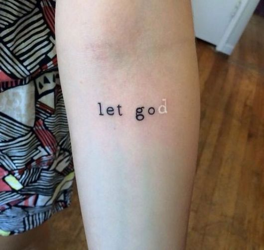"""Tatuagem escrita """"let god"""", toda a tattoo é feita com tinta preta exceto pelo """"d"""", que é feito com tinta branca"""