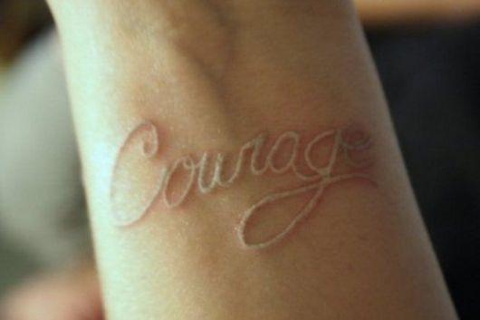 """Tatuagem branca escrita Courage ou """"Coragem"""""""