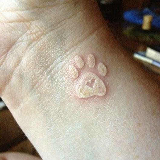 Tatuagem branca no pulso de uma pata de cachorro com um coração no centro