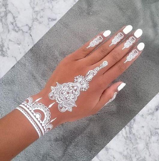 Tatuagem branca de mandala feito no pulso, no centro da mão e nos dedos