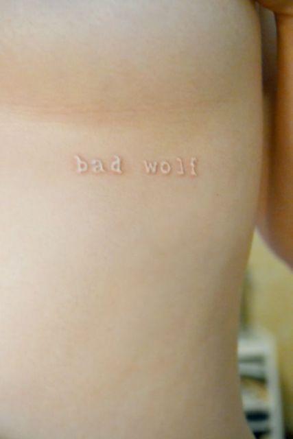 "Tatuagem branca escrita bad wolf ou ""lobo mau"""