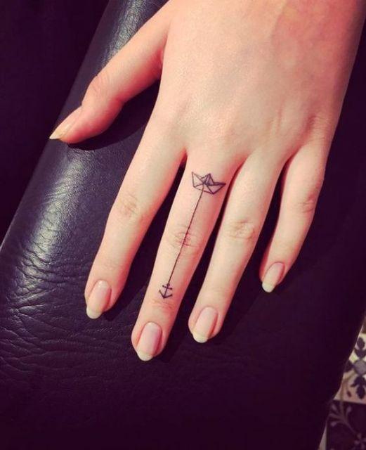 Tatuagem de um barco de papel no dedo com uma âncora que desce até perto da unha