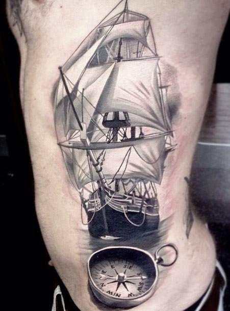 Tatuagem de um navio à vela visto de frente com uma bússola a sua frente