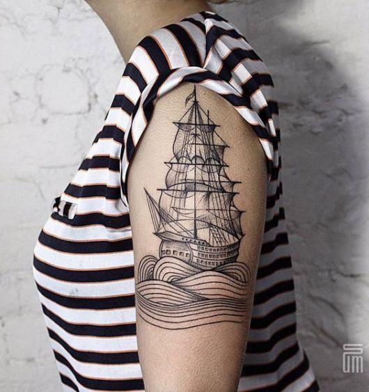 Tatuagem de um barco à vela navegando pelo mar no braço de uma mulher
