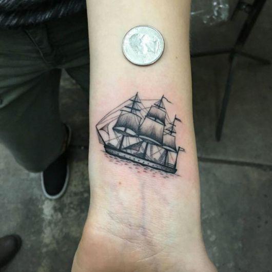 Tatuagem pequena de um barco à vela sombreado no pulso de uma pessoa
