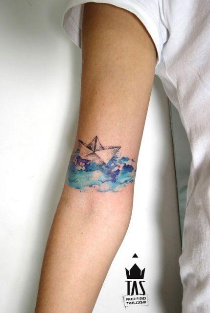 Tatuagem de um barco de papel flutuando sobre águas pintadas com aquarela azul