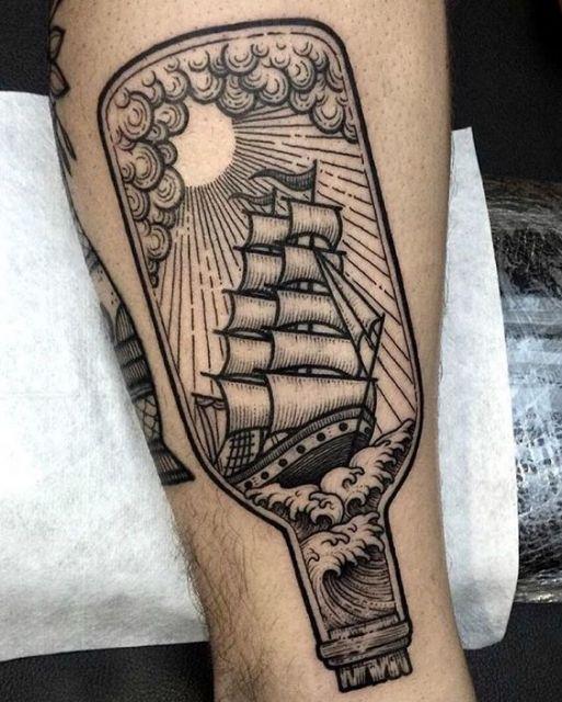 Tatuagem de um barco de velas navegando sob a luz do sol dentro de uma garrafa