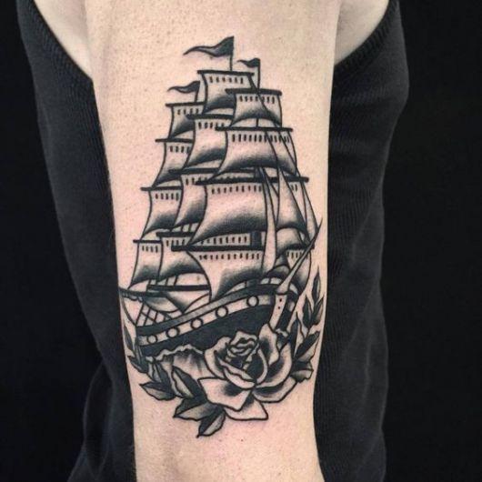 Tatuagem de um barco em preto e branco com muitas velas e uma rosa na parte de baixo