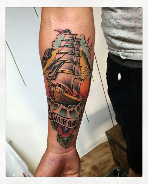Tatuagem de um navio pirata navegando com o sol em sua traseira pintado com cores vivas
