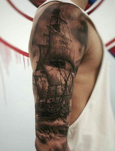 Tatuagem de um navio pirata muito realista cobrindo a parte superior do braço de um homem