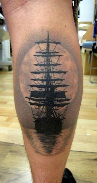Tatuagem de um navio pirata navegando em águas calmas com a lua enorme atrás