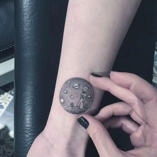 Tatuagem pequena no pulso do Pequeno Príncipe de pé, com estrelas e planetas ao fundo
