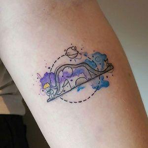 Tatuagem de um elefante dentro da barriga de uma jiboia pintada com aquarela roxa e azul
