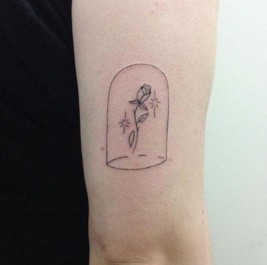 Tatuagem de uma Rosa dentro um compartimento. Ela é feita com linhas simples e sem cores.
