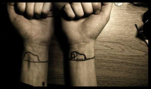Foto de dois pulsos tatuados. Em um há o desenho de uma cobra com um elefante dentro da barriga; na outra vemos a mesma foto, mas agora é possível ver o elefante dentro da barriga.