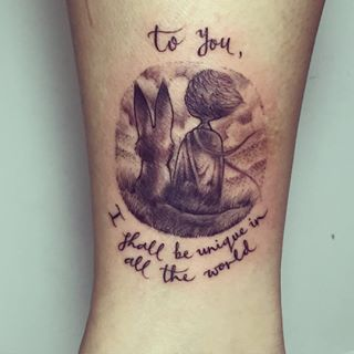 """Tatuagem do Pequeno Príncipe sentado ao lado da Raposa acompanhada pela frase """"Para você, eu serei o único em todo o mundo"""" em inglês"""