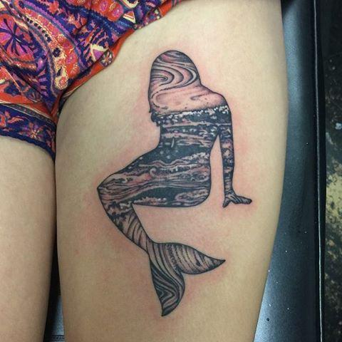 Tatuagem na coxa da silhueta de uma sereia preenchida com imagens do céu e do mar