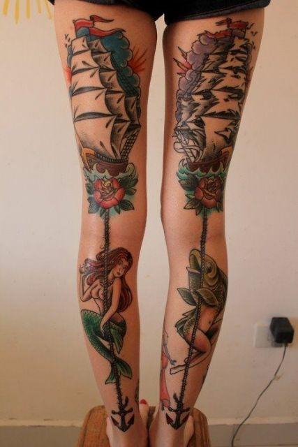 Tatuagem na parte traseira das pernas. Em uma perna, há um navio e uma sereia logo abaixo; na outra, há um navio com as velas rasgadas e uma criatura com cabeça de peixe e pernas de mulher logo abaixo.