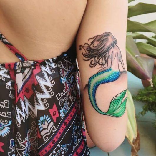Tatuagem de uma sereia na superior do braço que possui uma cauda colorida e cabelos aos ventos enquanto senta em uma pedra