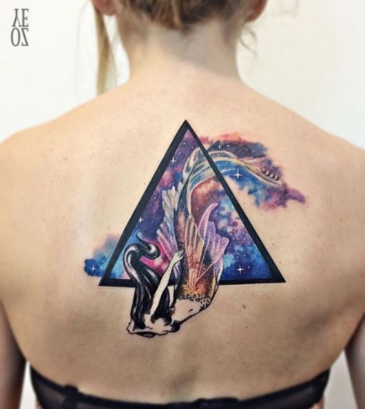 Tatuagem no centro das costas de uma sereia saindo de um triângulo tridimensional cujo interior é pintado de diversas cores diferentes.