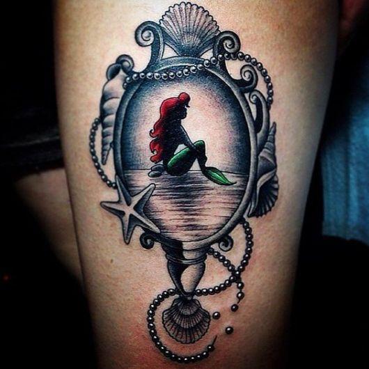 Tatuagem de um espelhos muito bonito que mostra em seu interior a Princesa Ariel sentada olhando para o horizonte