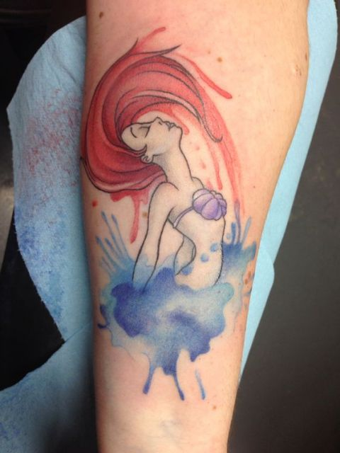 Tatuagem feita com aquarela da Princesa Ariel saindo da água enquanto joga seus cabelos vermelhos para trás